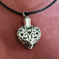 """Engravable Heart Urn Necklace.    ON HOLD Keep them close to your heart! Engravable stainless steel Heart Urn pendant on 18"""" black ribbon rope necklace. Front has black detail design. Opens at top (see pic 3). Can put your loved ones ashes, hair, or even soil from a grave side. can be engraved! Jewelry Necklaces"""