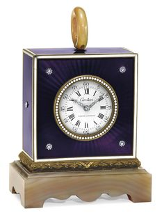 A BELLE ÉPOQUE DIAMOND, AGATE AND ENAMEL DESK CLOCK, BY CARTIER  With mechanical movement, the circular white dial with black Roman numerals and Arabic numerals, with rose-cut diamond hands within a beaded white border, to the purple enamel square-shaped case with rose-cut diamond detail and white enamel trim, to the sculpted agate base and top hoop, mounted in gold and silver, circa 1910