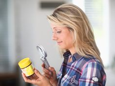 Mid adult woman using magnifying glass to look at ingredients on jar