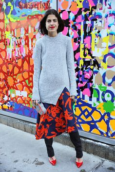 MAN REPELLER- Gray oversize sweater over colorful silky dress, skinny jeans underneath, bright pumps and playful clutch