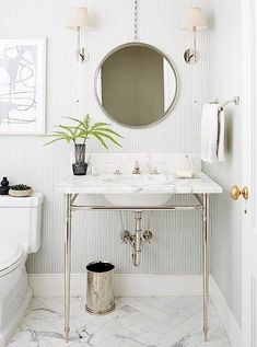 """The subtle wallpaper was the starting point of the powder room. """"We wanted something that was feminine but a bit masculine at the same time because it's five boys to one woman,"""" says Vivian. """"We also put marble on the floor and then carried that through with the vanity to keep a clean but warm feeling."""""""