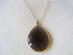 This lovely smokey quartz faceted stone is set in electroplated gold and has an amazing shimmer.  The stone hangs from a delicate gold diamond cut chain.