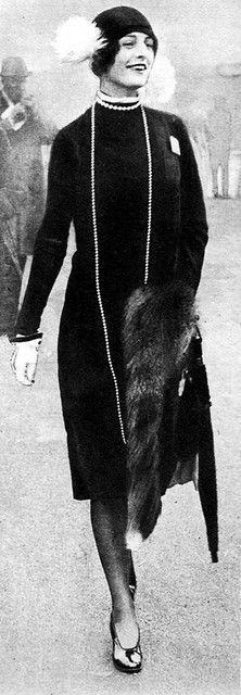 Fashion in 1926 vintage mid 20s style long sleek day dress black sleeves shift hat fur pearls elegant society woman