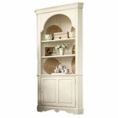 """Distressed wood corner cupboard with 3 display shelves and a bottom storage cupboard. Product: CupboardConstruction Material: WoodColor: LinenFeatures:Part of the Paula Deen Home CollectionTwo door storage area with adjustable shelfOval arch topDistressed finish Dimensions: 82"""" H x 43"""" W x 20"""" D"""