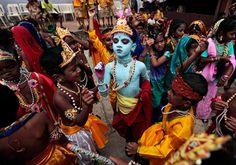Children dressed as Hindu God Krishna look on during festivities to mark Janmashtami at a school in Mumbai