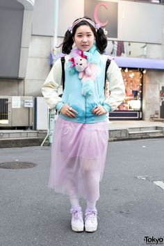 "Tsunamayomilk is a 16-year-old Harajuku girl with twintails and a kawaii sense of style who we street snapped near the popular Bubbles boutique.  Tsunamayomilk is wearing a Smile Camp Harajuku jacket with a sheer skirt from Sevens, white tights, and pastel GU shoes with lace socks. Accessories include a kawaii plush muffler, a stars headband, heart jewel rings, and a ""Love You"" backpack by the Japanese brand Swimmer."