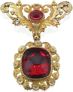 A 19th century garnet brooch, circa 1830 The large carbuncle garnet within a foliate tri-coloured gold surround suspended from a scrolling foliate surmount with central oval cabochon-cut garnet, closed back settings, length 55mm