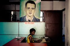 A Cuban office worker types under a painted portrait of the Cuban Revolutionary leader and poet Raul Gomez Garcia, hung on the wall of the Cuban state office in Santiago de Cuba, Cuba.