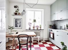 red and white chequered floor, light green kitchen cabinets.