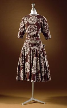 1947 printed cotton Dress by Edwin Hardy Amies, England. The dress has magyar sleeves (in which the armhole and upper arm are cut very wide, narrowing to the elbow and wrist), a tightly fitted bodice and a dropped waist. The circular skirt is embellished with a large bustle bow. Via V&A.