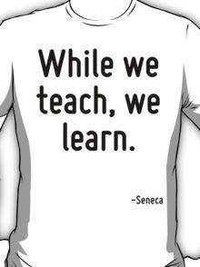 While we teach, we learn. T-Shirt