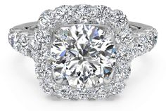 This scintillating designer engagement ring combines a halo of round diamonds surrounding the center stone with four large pave diamonds on either side of the 18k white gold band. This ring is made for a cushion cut diamond, but can also be set with a round diamond.