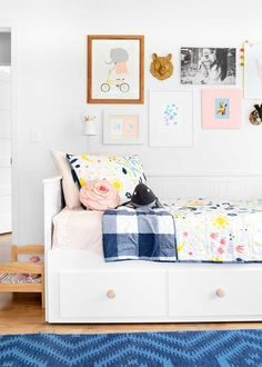Hallie's room in The Fauxhouse. A bright, kid-friendly room with thoughtful art, whimsical patterns, a place to play, and a bed to store toys. Nursery Decor, Room Decor, Wall Decor, Painted Rocking Chairs, Bright Pillows, Clock Painting, Doll Beds, Faux Taxidermy, Rattan Basket