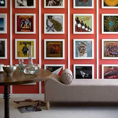 """Display album art collections:  Make a strong graphic statement by filling a bold painted wall with framed classic album covers. Vertical white stripes divide the space effectively and provide a punchy contrast for the bright coral background."""