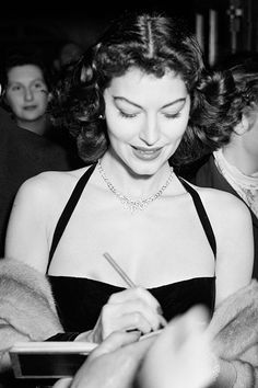 Ava Gardner signing autographs at a Midnight Matinee at the Colliseum, 1951.