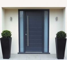 A navy blue door with oversized hardware is flanked by black boxwood planters and minimal silver sconces.