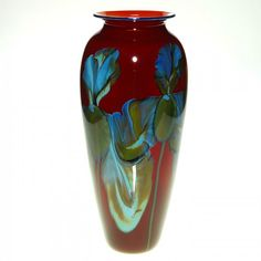 Richard Satava red vase displaying a gather of variegated blue irises larger than life, a 1994 creation