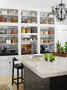 Fantastic wall of built-in open shelving for pantry staples and small kitchen appliances. White Shaker fronted cabinets pair with a black granite top.