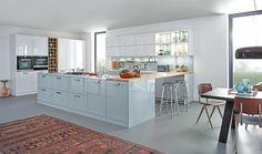 L'ambiance Carré-2-LG crée la surprise en proposant une esthétique bicolore laqué brillant sur des façades classiques. Les coloris pastel adoucissent l'ensemble, dans une dynamique fraîche et contemporaine. Contrepoint naturel à cette scène culinaire, le bar et l'étagère à vin en chêne. ©Leicht distribué par Show Home Concept (Chasse s/ Rhône)