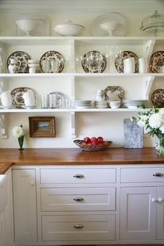 open shelving kitchen- everyday plates, bowls, white mugs, wine glasses, a few pieces of china, and some serving pieces