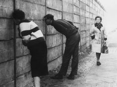West Berliners peer through the Berlin Wall into the Eastern sector near Checkpoint Charlie on October 3, 1966.