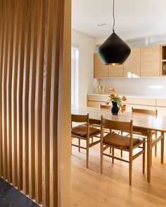 #kitchen | The dining area is separated from the entrance with a custom wrap-around screen that provides privacy without closing the space off completely. The slats are made of CNC'ed wood.