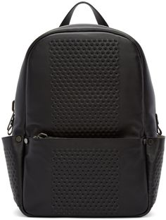 Structured buffed leather backpack in black. Perforated detailing and rivet accents throughout. Carry handle at top. Adjustable padded shoulder straps featuring detachable lanyard fastening. Zippered pocket at face. Patch pocket at sides. Padded panel at back face. Zip closure at main compartment. Patch pocket at interior. Suede lining in beige. Gunmetal-tone hardware. Tonal stitching. Approx. 11.5