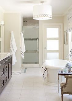 Elegant master bathroom design with tan walls paint color, Sherwin Williams Shoji white trim, freestanding soaking tub, Espresso bathroom cabinets, Silestone quartz counter tops, subway tiles shower surround, frosted glass shower door, Stonegate Astoria Pendant - white drum pendant with brass trim and bergere chair.