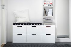 Chest with IKEA seating pad. Also full-length mirror and open storage on wall.