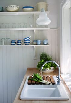 Love the open shelving, natural wood countertops and blue and white dishes. This white cottage kitchen feels open and inviting. #whitekitchen #openshelving