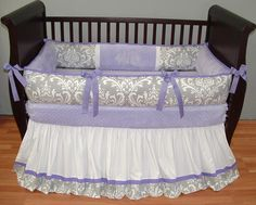 Brooklyn Lavender Baby Bedding  This custom 3 pc baby crib bedding set includes a luxury plush detailed bumper pad, long flowing trimmed crib skirt, and so soft lavender minky edged and backed blanket.  Designer silver and white damask, lavender grosgrain ties, soft lavender and white pique, and ultra soft pink minky combine softness and textured detail. Top quality and a modern touch for your little angel's nursery.