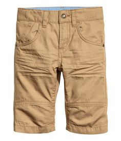 Camel. Clamdiggers in washed cotton fabric with an adjustable elasticized waistband, zip fly, snap fastener, and front and back pockets.