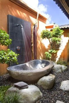 Relax outdoors among the rocks w/ this stunning outdoor bathtub with shower