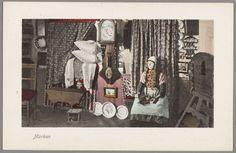 Vrouw in dracht poseert in Marker interieur voor een gordijn van druivengoed waarachter de bedstede. In het midden een Friese staartklok (bruidsklok met latoenkoperen rand op de wijzerplaat). Rechts een opgeklapte flap aan de wand (opklaptafel). Verder een houten stoof en geborduurde kussens in de bedstee-opening. 1908-1930 #NoordHolland #Marken