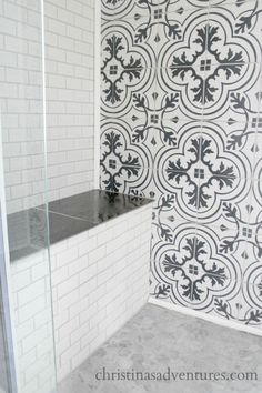 built in bench in shower with subway tile and black and white patterned tile and marble hex tile floor