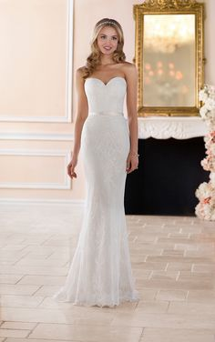 This classic lace sheath wedding dress by Stella York is simply a dream come true! Lace over Lavish satin creates a column silhouette complete with a sweetheart neckline and natural waistline. The soft lace of this sleek wedding dress slims and shapes your silhouette into the perfect hourglass figure. Romantic eyelash lace completes the hemline for a very polished feel. The back of the dress is finished by an easy-close zipper under delicate fabric buttons and a detachable satin sash. This…