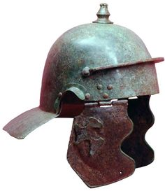 """Weisenau helmet, mid 1st century A.D. Type with a distinct variation (a feature not observed elsewhere): two iron cheekpieces with copper edging and the remainder of a  figural brass decoration on the right cheekpiece. The helmet belongs to a relative small group of Weisenau helmets without """"eyebrows"""" and articulated horizontal ribs at the back of the skull, neckguard is entirely plain, frontal protective bar carries a three letter inscription underside Private collection"""