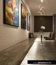 white brick wall. cement screed flooring and bench. Posters with spotlights.