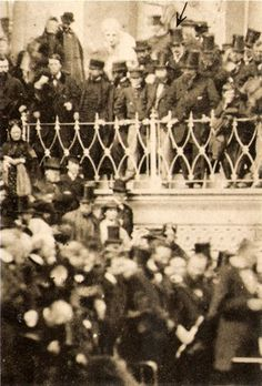 Arrow points to John Wilkes Booth in top hat listening to Lincoln deliver his speech during  the President's Second Inauguration Event. *s*