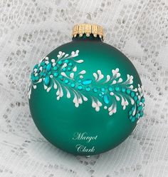 Margot Clark created this Blue Green colored glass ornament with White 3D texture painted MUD scroll design with added rhinestone bling. Each ornament created is a one-of-a-kind. The texture medium and paint brush I use to paint the ornaments were both created to my specifications. My signature M is located on the bottom of the ornament. Gift boxed. Measures 2 1/2 x 2 1/2 Ornament weight is 2 ounces.