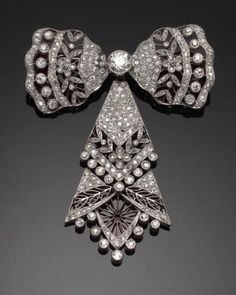 An elegent belle epoque diamond-set bow brooch The central sections of the bow…