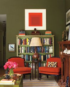 Matching red chairs and a graphic red print pop against olive green walls