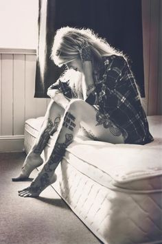 Black and white photo. Leg tattoos. Plaid shirt. No pants. Kitten. Blonde.
