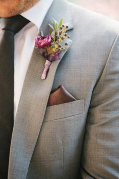 This plum colored boutonniere looks great with a gray suit! Photography by @Sylvie Gil