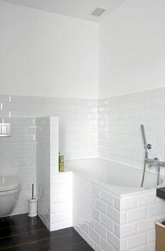 Badet er rent og enkelt innredet i svart og hvitt. Hvite subway-fliser dekker halve veggen, og svøper inn badekaret.