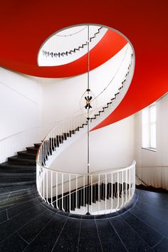 spiral staircase with granite flooring and red ceiling