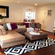 Black and white area rug in the living room. Pops of fuschia too. Sectional sofa.