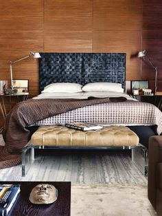 This bedroom contrasts warm wood walls with a dark leather headboard #home #decor