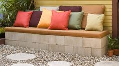 DIY Concrete Patio Bench for $30 - If you're looking to increase your backyard entertaining space on a budget consider making this concrete patio bench. You'll put together the sides with concrete blocks and the top is a wooden plank covered with scrap foam padding and outdoor fabric.