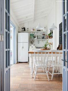 Cozinha com clima de casa de praia: piso de madeira, móveis brancos e porta pintada de azul.